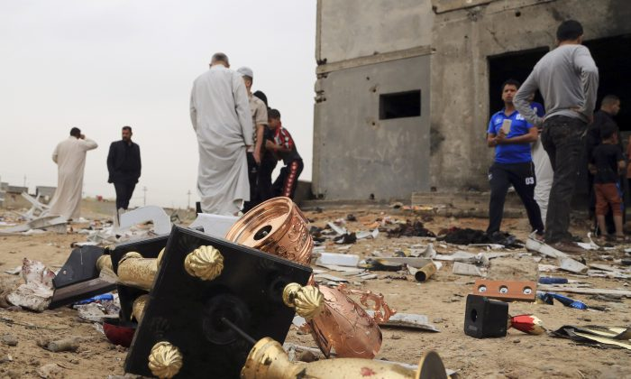 Broken Cups lie on the ground as people inspect the aftermath of a suicide bombing at a soccer field in Iskandariya, 25 miles (about 40 kilometers) south of Baghdad, Iraq, Saturday, March 26, 2016. A suicide bomber killed and wounded dozens in an attack on a crowd gathered at a soccer stadium south of Baghdad on Friday. (AP Photo/Karim Kadim)
