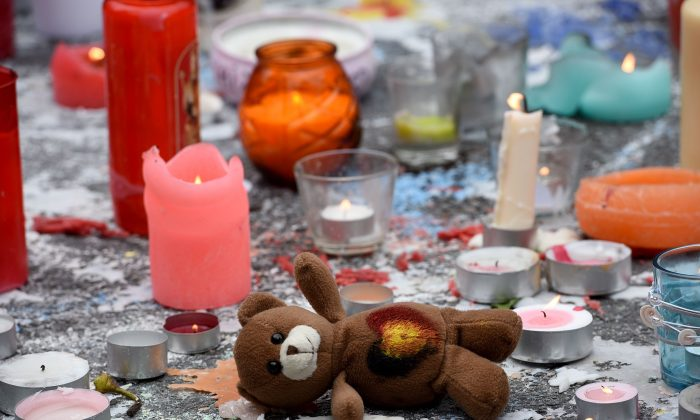 A teddy bear layed next to candles as people gather to observe a minute of silence in memory of the victims of the Brussels airport and metro bombings, on the Place de la Bourse in central Brussels on March 23, 2016, a day after the triple blasts killed more than 30 people and left other 300 injured. (Patrick Stollarz/AFP/Getty Images)
