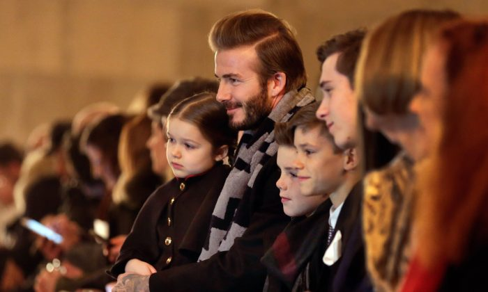 David Beckham and his three sons wait for the the Victoria Beckham Fall 2016 collection to be modeled during Fashion Week in New York, Feb. 14, 2016. (AP Photo/Richard Drew)