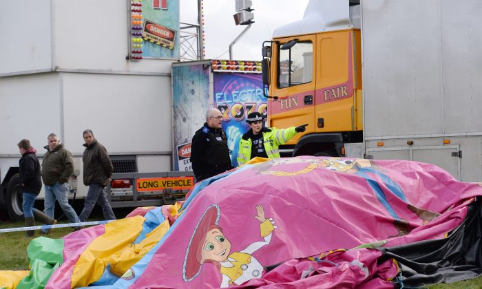 Police and forensic officers attend the scene Sunday, March 27, 2016, where a seven-year old girl died after she was blown by the wind about 150 metres on a bouncy castle on Saturday. The children's bouncy castle is thought to have been swept away by a gust of wind as families gathered for an Easter fair, over the long holiday weekend. (Stefan Rousseau/PA via AP)