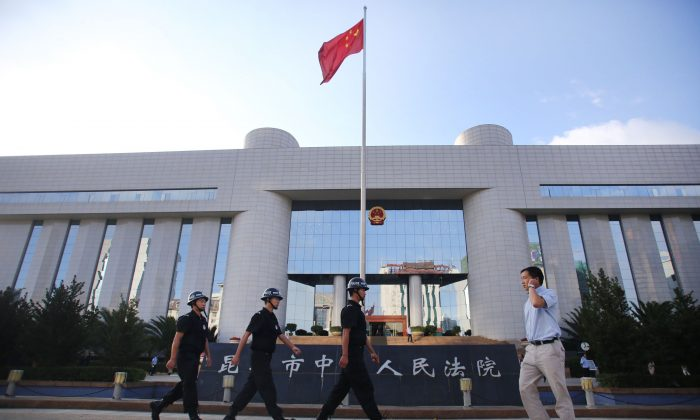 Police patrol at the gate of Kunming's Intermediate Court in Kunming, southwest China's Yunnan province on September 12, 2014. On March 23, 2016, a local representative to the National People's Congress walked away from a district court in Chang'an after hitting a lawyer in the face. In (STR/AFP/Getty Images)