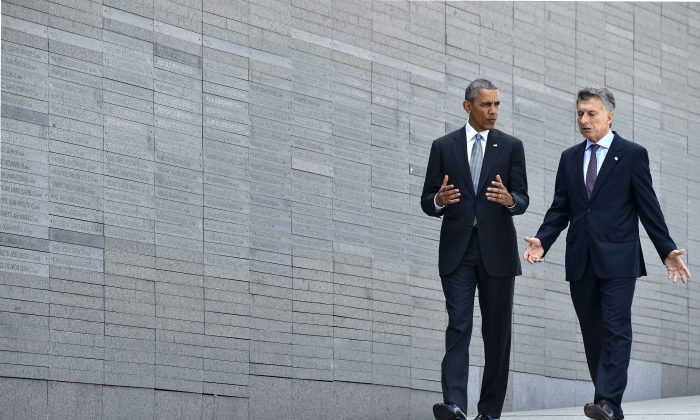 "President Barack Obama (L) walks with Argentine President Mauricio Macri as he pays homage to the victims of Argentina's ""dirty war"" at the Parque de la Memoria (Remembrance Park) in Buenos Aires on March 24, on the 40th anniversary of the 1976 military coup. Obama paid tribute to victims of Argentina's former Washington-backed dictatorship at a memorial on the banks of the River Plate, a monument to the estimated 30,000 people who were killed or went missing under the 1976-1983 military regime. (Nicholas Kamm/AFP/Getty Images)"