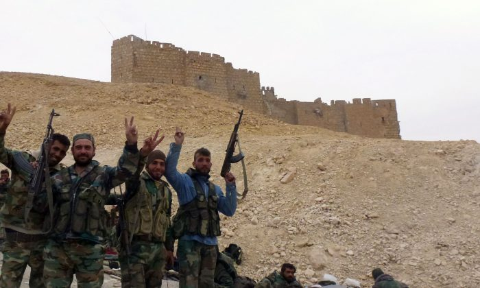 Syrian pro-governement forces gesture next to the Palmyra citadel on March 26, 2016, during a military operation to retake the ancient city from the jihadist Islamic State. (Maher al-Mounes/AFP/Getty Images)