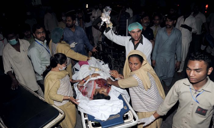 Pakistani relatives and emergency workers carry an injured woman to the hospital in Lahore on March 27, 2016, after at least 56 people were killed and more than 200 injured when an apparent suicide bomb ripped through the parking lot of a crowded park in the Pakistani city of Lahore where Christians were celebrating Easter. (Arif Ali/AFP/Getty Images)