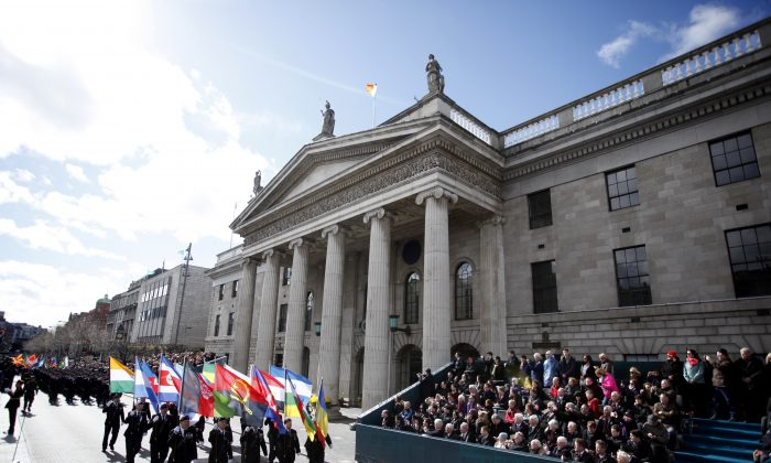 Thousands of soldiers marched solemnly Sunday, March 27, 2016 through the crowded streets of Dublin to commemorate the 100th anniversary of Ireland's Easter Rising against Britain, a fateful rebellion that reduced parts of the capital to ruins and inspired the country's eventual independence. (AP Photo/Peter Morrison)