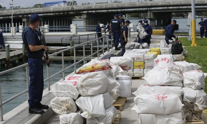 A U.S. Coast guardsman stands guard over bales of cocaine and marijuana as part of an estimated $41 million worth of drugs at the Coast Guard Base Miami Beach, Tuesday, Sept. 29, 2015, in Miami Beach, Fla.  (AP Photo/Lynne Sladky)