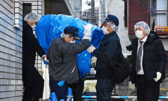 Police officers carry sheet-covered computer from the apartment of abduction suspect Kabu Terauchi in Tokyo Monday, March 28, 2016. Japanese police captured the 23-year-old man in an abduction case after a teenage girl escaped and ran for freedom a day earlier after being held captive in his apartment for nearly two years. (Kyodo News via AP)