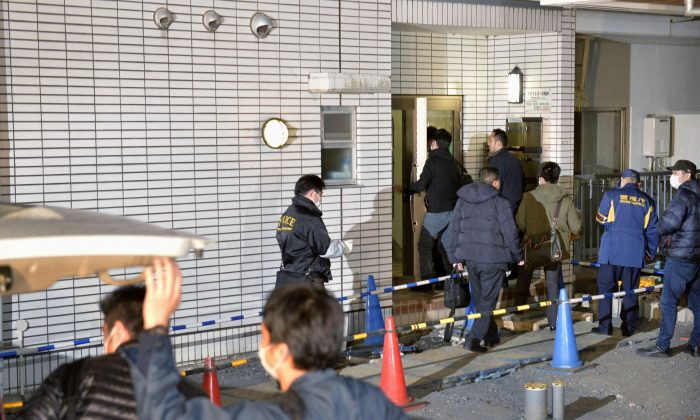 Police officers arrive for investigation of the apartment of abduction suspect Kabu Terauchi in Tokyo on Monday (Kyodo News via AP)