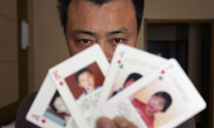 """The """"missing children playing cards"""" are displayed by Shen Hao, founder of the missing person wetsite XRQS.com, in Beijing, China, on March 31, 2007. The cards show photographs, informations of 27 missing children and Shen Hao plans to hand them out for free to the public security departments, civil affairs bureaus, and residents, in areas notorious for child trafficking. Shen, 38, a resident in Chuzhou of central China's Anhui Province, set up the wetsite in 2001 and later founded a network of volunteers dedicated to finding missing people. (China Photos/Getty Images)"""