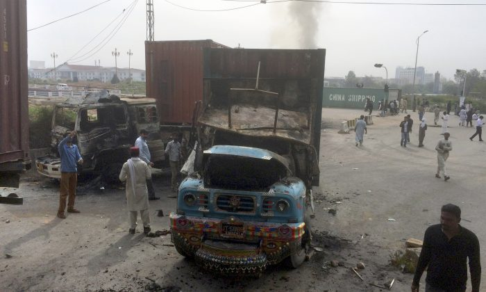 People look at trucks burnt by supporters of the religious party Sunni Tehreek during a march toward the parliament building in Islamabad, Pakistan, Monday, March 28, 2016. Thousands of demonstrators marched into the Pakistani capital to protest the hanging of Qadri, charged with murdering a secular governor. Police officer Muhammad Nasim said that the march of thousands people was peaceful initially, but as the crowds reached an avenue leading to parliament the protesters turned violent, smashing windows and damaging bus stations. (AP Photo/Anjum Naveed)