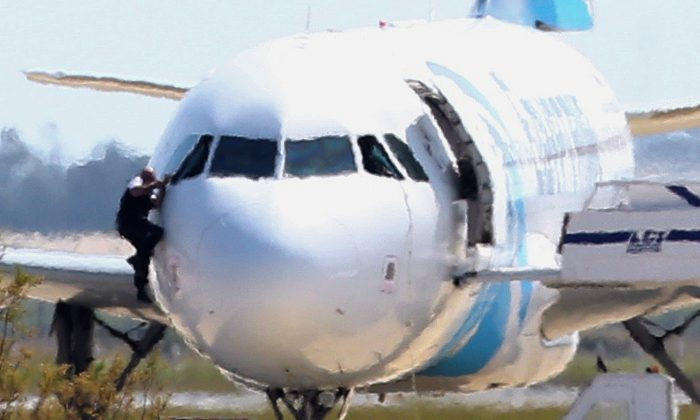 A man, leaves the hijacked aircraft of Egyptair from the pilot's window after landing at Larnaca airport Tuesday, March 29, 2016. (AP Photo/Petros Karadjias)