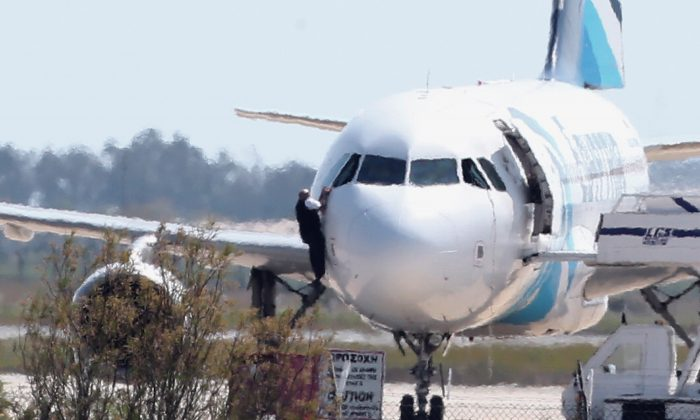 A man  leaves the hijacked aircraft of Egyptair from pilot window at Larnaca airport in Cyprus Tuesday, March 29, 2016. (AP Photo/Petros Karadjias)