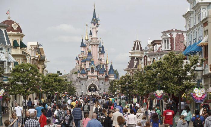 Visitors walk near Sleeping Beauty's Castle at Disneyland during happier times.  (AP Photo/Michel Euler)
