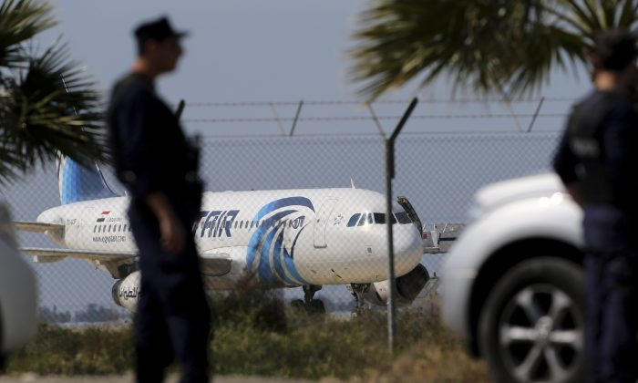 Police officers stand guards by the fence of the airport as a hijacked EgyptAir aircraft is seen after landing at Larnaca Airport in Cyprus Tuesday, March 29, 2016. The EgyptAir plane was hijacked on Tuesday while flying from the Egyptian Mediterranean coastal city of Alexandria to the capital, Cairo, and later landed in Cyprus where some of the women and children were allowed to get off the aircraft, according to Egyptian and Cypriot officials. (AP Photo/Petros Karadjias)