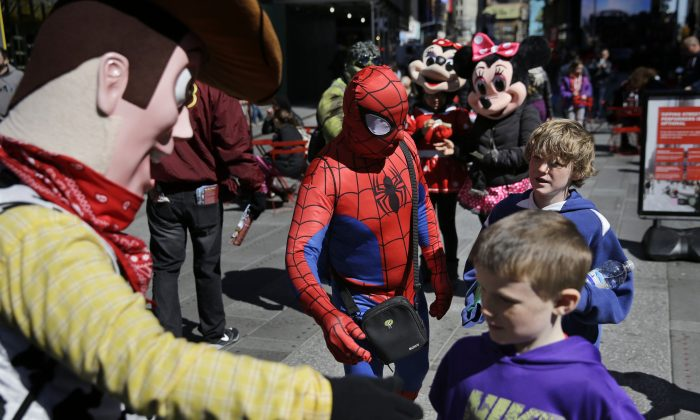 Costumed characters approach kids walking through Times Square in New York, Tuesday, March 29, 2016. The costumed characters, naked painted ladies and bus tour ticket sellers who have made all of Times Square their stomping grounds could be restricted to specific zones under legislation being considered by the City Council. The council's committee on transportation is holding a hearing Wednesday morning on legislation that would allow the city's Department of Transportation to create rules and regulations for pedestrian plazas like the ones in Times Square. (AP Photo/Seth Wenig)
