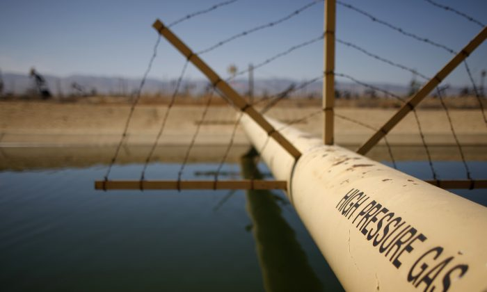 A high pressure gas line crosses over a canal in an oil field over the Monterey Shale formation where gas and oil extraction using hydraulic fracturing, or fracking, takes place, near Lost Hills, Calif., on March 23, 2014. (David McNew/Getty Images)
