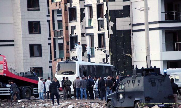 Security and forensic officers work at the site after an explosion caused by a bomb-laden car targeting police in the mainly Kurdish city of Diyarbakir, Turkey, Thursday, March 31, 2016, Turkish news agencies reported. (AP Photo/Mahmut Bozarslan)