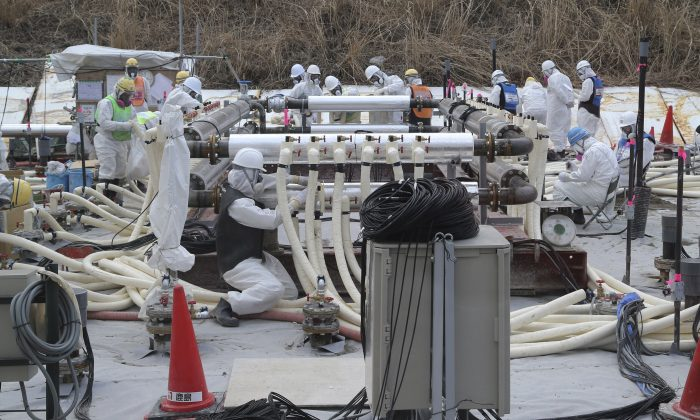 In this March 10, 2014 file photo, workers wearing protective gears install a trial model of the underground frozen wall at the Fukushima Dai-ichi nuclear power plant in Okuma, Fukushima prefecture, northeastern Japan in their attempt to stop the leakage of radioactive water that has accumulated at the crippled nuclear power plant. (AP Photo/Koji Sasahara, Pool)