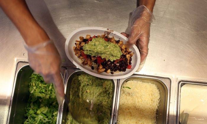 Chipotle restaurant workers fill orders for customers. (Photo by Joe Raedle/Getty Images)