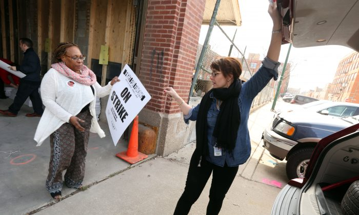 In this Wednesday, March 30, 2016 photo, Chicago Public School teachers Tammie Vinson, left, and Katie Sciarine, right, both of Oscar DePriest School, load signs in their vehicles in preparation for Friday's one-day teachers strike in Chicago. Chicago Teachers Union staff passed out picket signs and flyers to teachers at CTU headquarters. The teachers union and other community groups and unions are calling for more state funding for schools and social services. (Phil Velasquez /Chicago Tribune via AP)