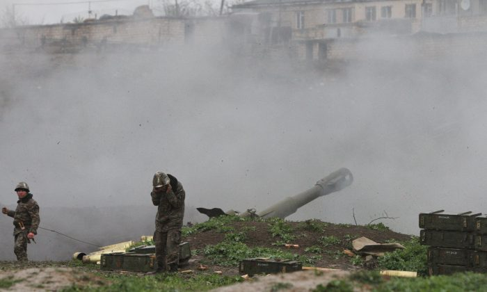 Armenian servicemen of the self-defense army of Nagorno-Karabakh fire an artillery shell towards Azeri forces from their positions in the town of Martakert in Armenian-seized Azerbaijani region of Nagorny-Karabakh on April 3, 2016. Clashes between Azerbaijani and Armenian forces rumbled on April 3, despite Baku announcing a cease-fire after the worst outbreak of violence in decades over the disputed Nagorny-Karabakh region sparked international pressure to stop fighting. (Vahram Baghdasaryan/AFP/Getty Images)