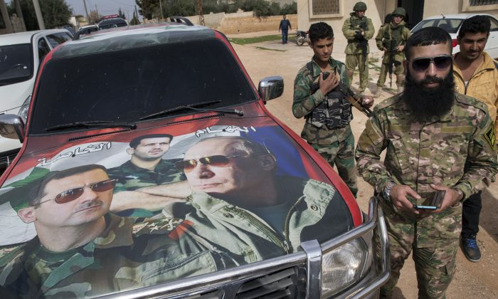 Syrian and Russian soldiers, who escort a group of journalists in the background, stand near a car covered by collage showing photos of faces of Russian President Vladimir Putin (R), Syrian President Bashar Assad (L), and a Syrian general, President's Assad brother, Maher Assad (C), in Maarzaf, about 10 miles west of Hama, on March 2, 2016. (Pavel Golovkin/AP Photo)