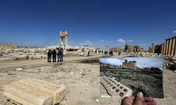 A general view taken on March 31, 2016 shows a photographer holding his picture of the Temple of Bel taken on March 14, 2014 in front of the remains (far-L) of the historic temple after it was destroyed by Islamic State (IS) group jihadists in September 2015 in the ancient Syrian city of Palmyra. Syrian troops backed by Russian forces recaptured Palmyra on March 27, 2016, after a fierce offensive to rescue the city from jihadists who view the UNESCO-listed site's magnificent ruins as idolatrous.   / AFP / JOSEPH EID        (Photo credit should read JOSEPH EID/AFP/Getty Images)
