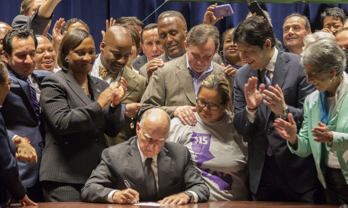 California Governor Jerry Brown signs landmark legislation SB 3 into law in Los Angeles on April 4, 2016. (David McNew/Getty Images)