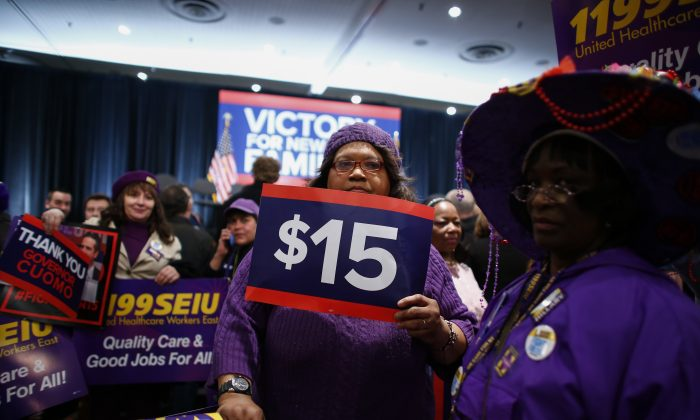 """A woman holds banners before Democratic presidential candidate Hillary Clinton speaks during a event named as a """"victory rally for $15 minimum wage and paid family leave"""" at the Javitz Center in New York on April 4, 2016. (Kena Betancur/AFP/Getty Images)"""