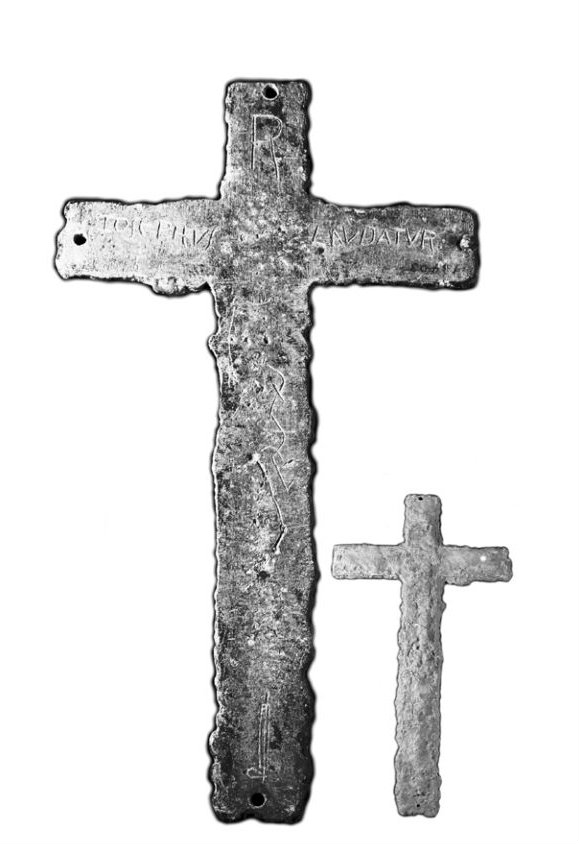 A lead cross, about 12 inches tall. The inscription reads,