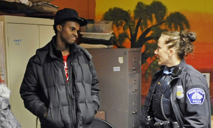 In this Jan. 14, 2011 photo, Abdirizak Mohamed Warsame visits with Minneapolis police Officer Jeanine Brudenell during an event for Somali youth at a Minneapolis community center. Warsame was arrested by federal authorities in December 2015 and recently pleaded guilty to terror charges. His arrest shocked many, because he had been surrounded by positive influences. (AP Photo/Jim Mone)