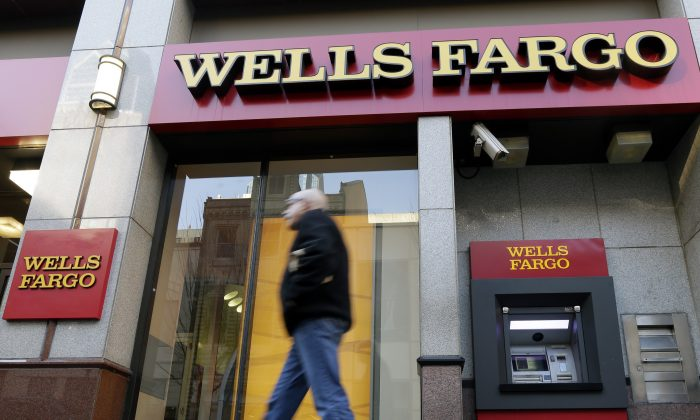 In this Wednesday, Dec. 19, 2012, file photo, a man walks past a Wells Fargo location in Philadelphia. (AP Photo/Matt Rourke)