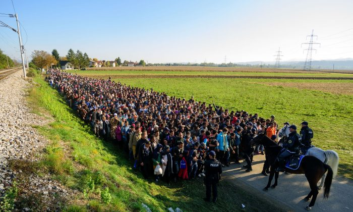 Police escort migrants and asylum seekers as they walk to a refugee center after crossing the Croatian-Slovenian border near Rigonce on Oct. 24, 2015. (Jure Makovec/AFP/Getty Images)