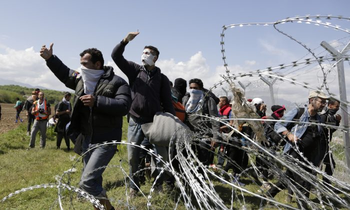 A group of migrant men call to others during protests at a fence at the northern Greek border point of Idomeni, Greece, on April 10, 2016. Thousands of migrants protested at the border and clashed with Macedonian police. (AP Photo/Amel Emric)