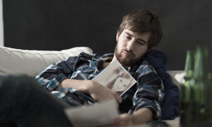Devastated sad man with a photo of ex girlfriend
