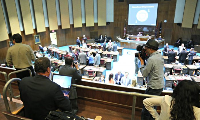 Arizona Republic photographer Nick Oza and Associated Press journalist Bob Christie report from the gallery of the Arizona House of Representatives after reporters were denied access to the floor pending criminal and civil background checks, in Phoenix on Thursday, April 7, 2016. (AP Photo/Ryan VanVelzer)