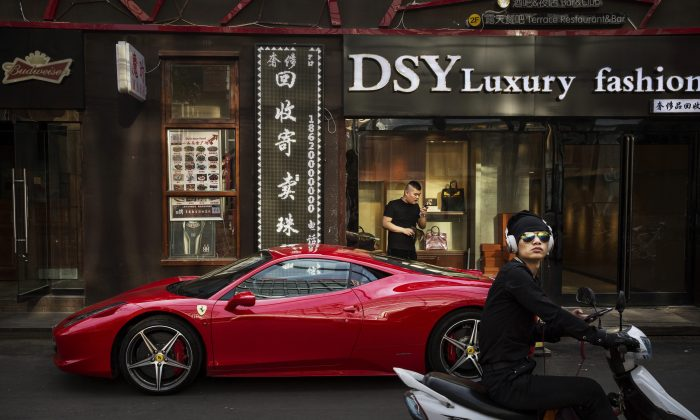 A Chinese man uses his phone next to his Ferrari in an upscale shopping district in Beijing on May 29, 2015. (Kevin Frayer/Getty Images)