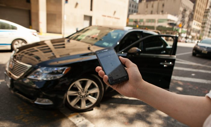 A person with a smartphone displaying the Uber app, before getting in a  black Lexus which was hailed using the app, in Manhattan, on June 8, 2014. (Benjamin Chasteen/Epoch Times)