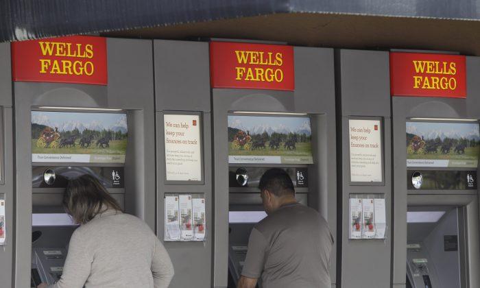 Customers use Wells Fargo Bank ATM machines in Santa Clara, Calif., on April 18, 2011. (AP Photo/Paul Sakuma)