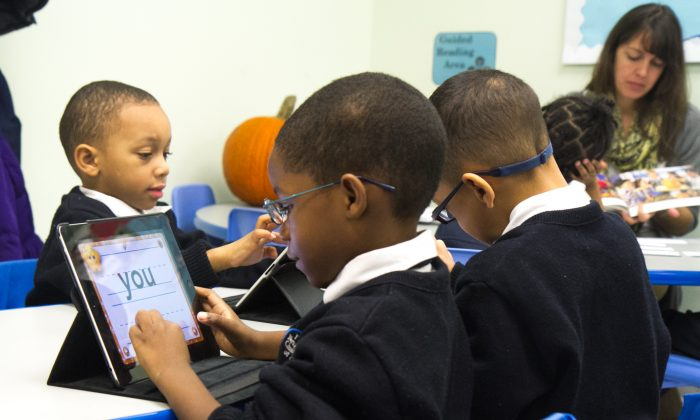First graders at a charter school in New York use Apple iPads as one of their tools to learn to read and write in this file photo. (Benjamin Chasteen/The Epoch Times)