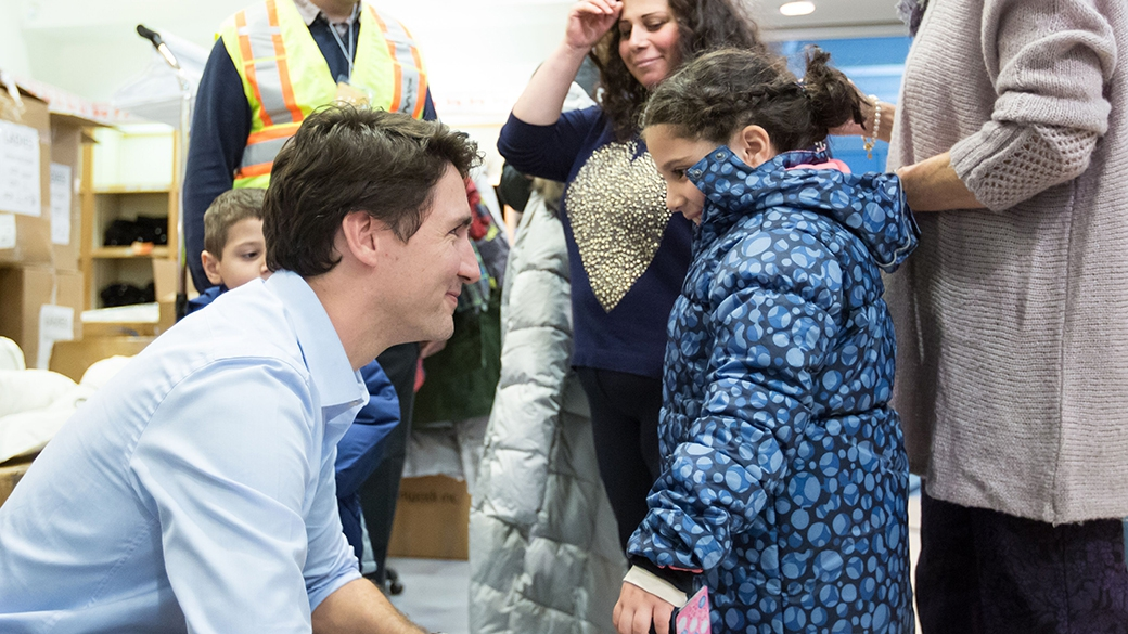 Canadian Prime Minister Justin Trudeau welcomes Syrian refugees to Canada late at night at Pearson International airport in Toronto, Dec. 10, 2015. (PMO Canada)