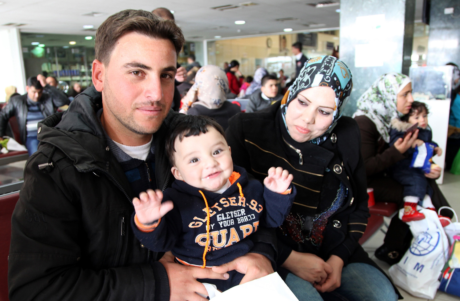 Radi poses for a photo with his son and wife while waiting in an airport in Amman, Jordan, to board a plane to Canada where they will be resettled, on Dec. 20, 2015. (AP Photo/Sam McNeil)