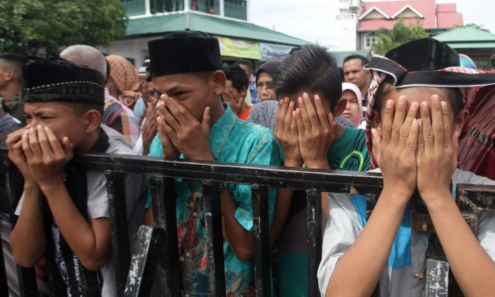 Acehnese youths react as they watch a public caning for those who are convicted of violating local Sharia law, in Banda Aceh, Aceh province, Indonesia, Friday, Nov. 6, 2015.  (AP Photo/Heri Juanda)