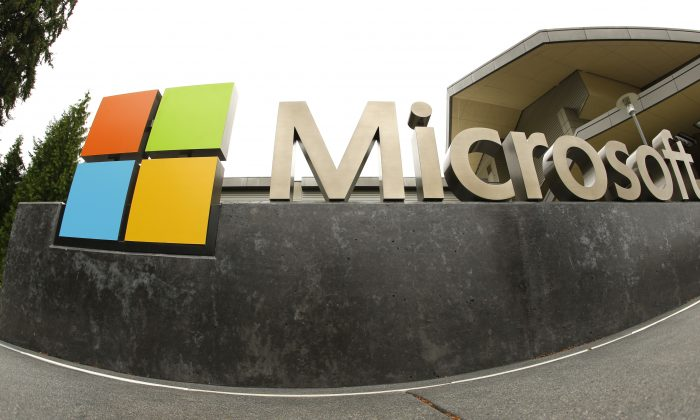FILE - This July 3, 2014, file photo, shows the Microsoft Corp. logo outside the Microsoft Visitor Center in Redmond, Wash. In a lawsuit filed Thursday, April 14, 2016, Microsoft is suing the U.S. government over a federal law that lets authorities examine its customers' email or online files without the customers' knowledge. The lawsuit comes as the tech industry is increasingly butting heads with U.S. officials over customers' privacy rights. (AP Photo Ted S. Warren, File)