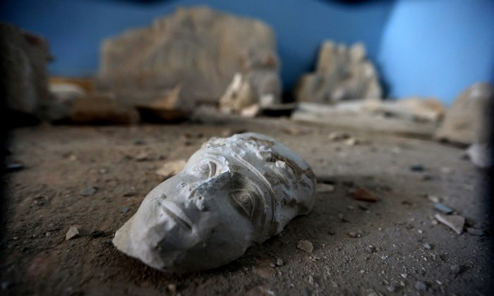 The face of a statue lies on the ground at the destroyed museum in the ancient Syrian city of Palmyra on March 31, 2016.  (Joseph Eid/AFP/Getty Images)