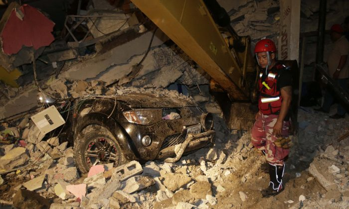 A rescue worker searches in the rubble of a destroyed house in the Pacific coastal town of Pedernales, Ecuador, on April 17, 2016. The strongest earthquake to hit Ecuador in decades flattened buildings and buckled highways along its Pacific coast, sending the Andean nation into a state of emergency. (AP Photo/Dolores Ochoa)