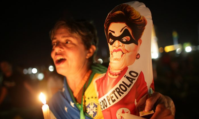 "An Anti-government demonstrator holds a caricature of Brazil's President Dilma Rousseff wearing a bandit mask and sash that reads in Portuguese ""Big oil"" outside Congress where lawmakers debate whether to oust the Brazilian President Dilma Rousseff in Brasilia, Brazil, on April 16, 2016. Sunday's vote will determine whether the impeachment proceeds to the Senate. Rousseff is accused of violating Brazil's fiscal laws to shore up public support amid a flagging economy. (AP Photo/Eraldo Peres)"