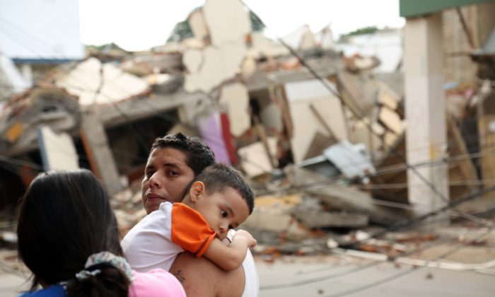 A man holds a child next to a collapsed building caused by a 7.8 earthquake in Portoviejo, Ecuador, Sunday April 17, 2016. A magnitude-7.8 quake, the strongest since 1979, hit Ecuador flattening buildings, buckling highways along its Pacific coast and killing hundreds. (AP Photo/Carlos Sacoto)