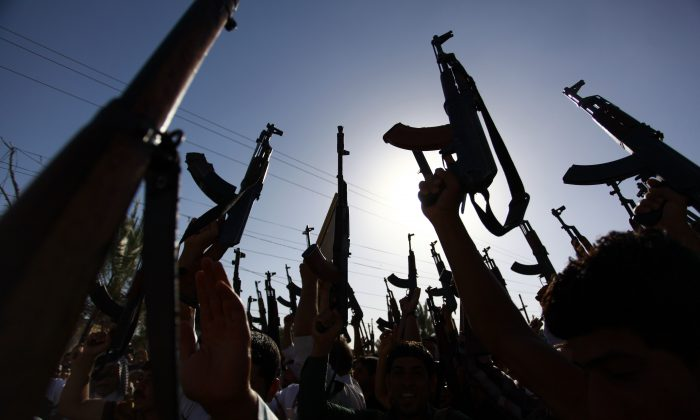 Iraqi Shiite tribesmen brandish their weapons as they gather to show their willingness to join Iraqi security forces in the fight against Jihadist militants who have taken over several northern Iraqi cities, on June 17, 2014, in the southern Shiite Muslim shrine city of Najaf. (Haidar Hamdani/AFP/Getty Images)