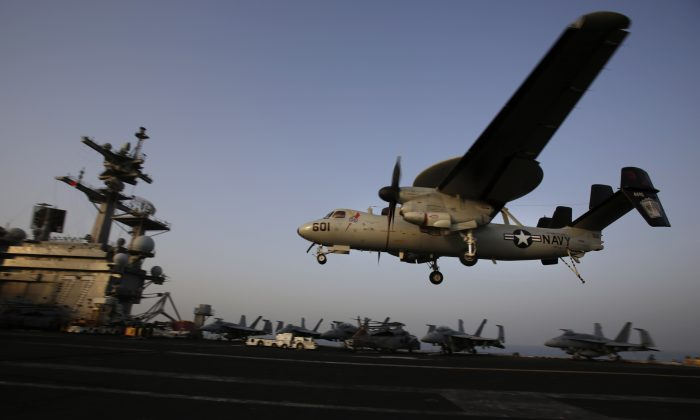 An aircraft lands after missions targeting the Islamic State in Iraq from the deck of the U.S. Navy aircraft carrier USS George H.W. Bush in the Persian Gulf on Aug. 10, 2014. (AP Photo/Hasan Jamali)